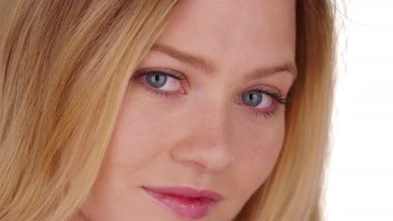Thumbnail for Close-up portrait of pretty blonde woman with blue eyes on white backdrop