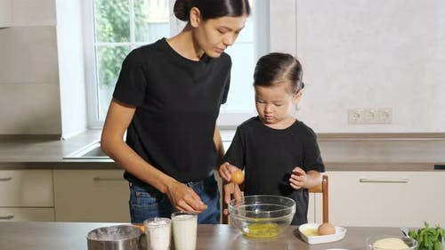 Woman and Little Girl Cooking in the Kitchen