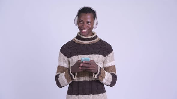 Thumbnail for Young Happy African Man Thinking While Using Phone Ready for Winter