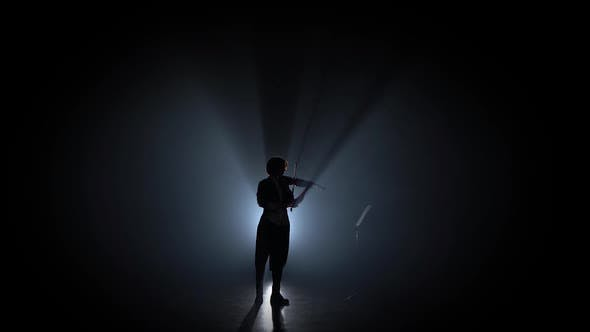 Thumbnail for Woman Plays the Violin and Looks at the Music Stand in the Dark . Silhouette. Black Smoke Background