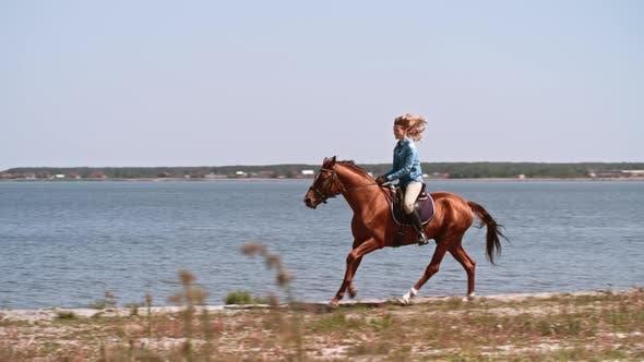 Woman Galloping by Lake on Horseback