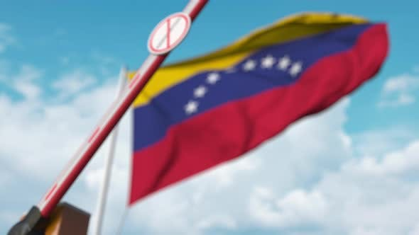 Closing Barrier with Stop Immigration Sign at the Venezuelan Flag