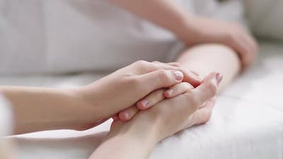 Hands of Woman Supporting Female Patient