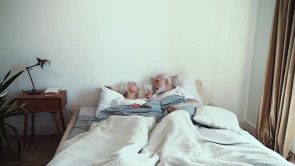Old couple waking up in the morning.