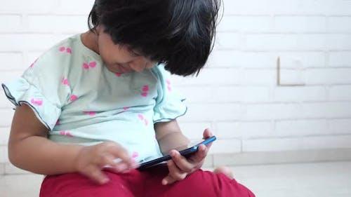 Kindermädchen, das Cartoon auf dem Smartphone beobachtet