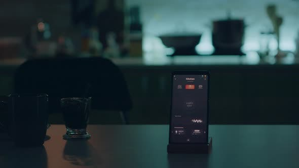 Smart Home Application on Phone Placed on Kitchen Desk in Empty House