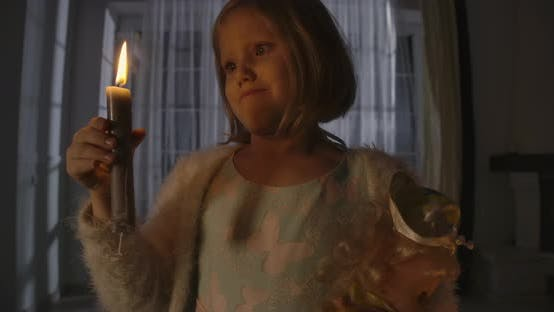 Thumbnail for Close-up Portrait of Strange Caucasian Girl Blowing Out Candle and Holding Doll in Other Hand
