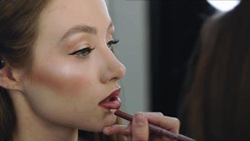 Closeup of Girl with Perfect Nude Makeup and Makeup Artist