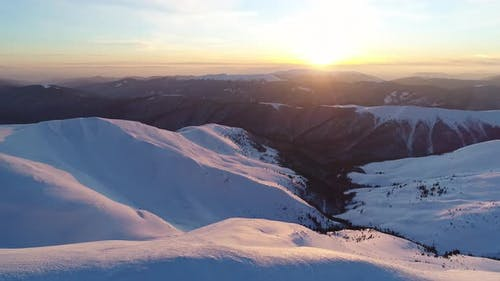 Flight over the snowy mountains illuminated by the evening sun