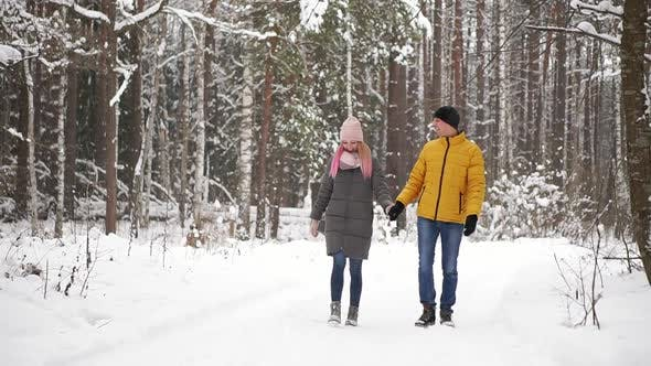 Thumbnail for A Man in a Yellow Jacket and a Girl in a Hat and Scarf Walk Through the Winter Forest During a