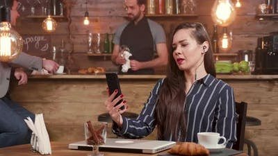 Young Businesswoman Engaged in a Video Call in a Coffee Shop