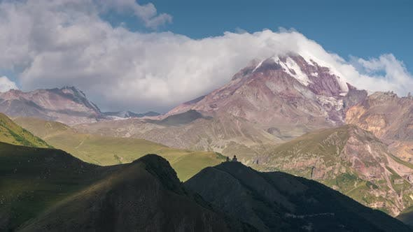Thumbnail for Caucasian Highland. Old Church and Kazbek Mountain Peak with Snow Cap Sun Rays with Moving Shadows
