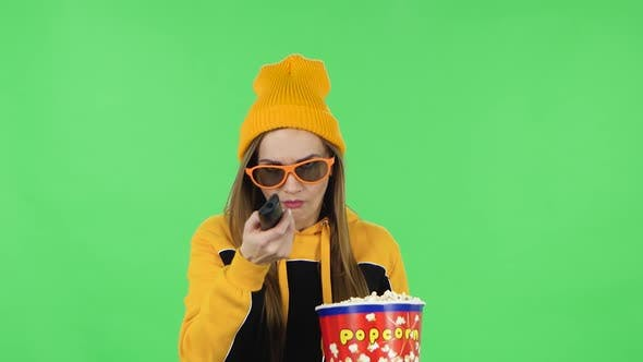 Thumbnail for Portrait of Girl in Yellow Hat in 3D Glasses Is Watching TV and Eating Popcorn with TV Remote in Her