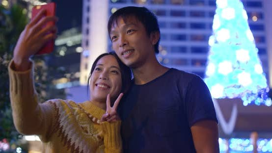 Thumbnail for Couple take selfie in the city at night