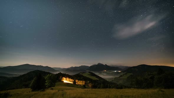 Thumbnail for Stars in Starry Sky over Mountains and Foggy Rural Landscape at Moonlight Night to Day