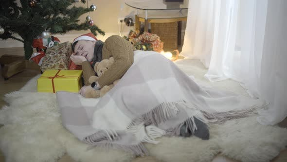 Thumbnail for Wide Shot of Happy Young Man Sleeping on Gift Boxes at Christmas Tree at Home