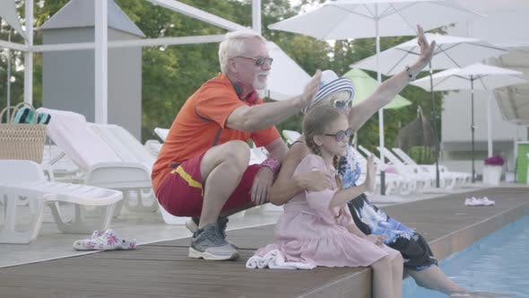 Thumbnail for Happy Mature Couple on the Edge of the Pool Hugging Little Granddaughter