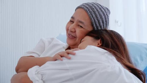 Young daughter encourages and comforts a mother with cancer during hospitalization.