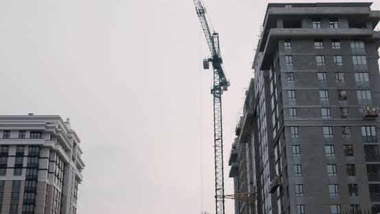 Thumbnail for Crane working on construction site under grey cloudy sky on rainy day