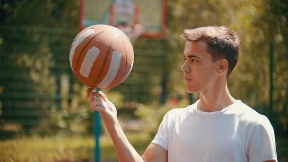 Thumbnail for A Young Handsome Man Standing on a Sports Ground and Spinning the Basketball Ball on His Finger