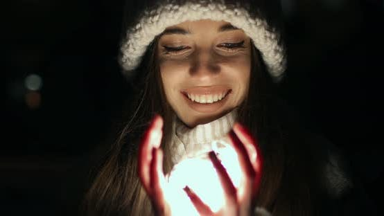 Thumbnail for Girl Unfolding Hands Filled with Small Decoration Lights