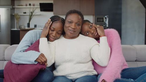 Caring Mom and Adolescent Daughters Bonding on Couch
