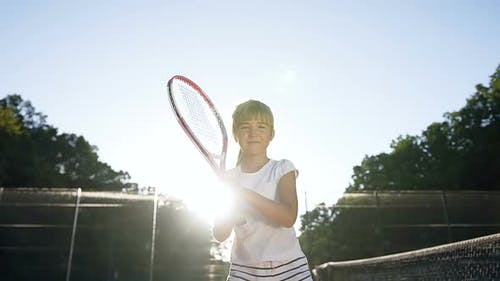 Little Girl with Tennis Racket Walking on the Court
