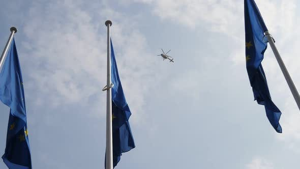 Cover Image for Three EU Flags Like Symbols with a Police Copter on the Background in Slo-mo.