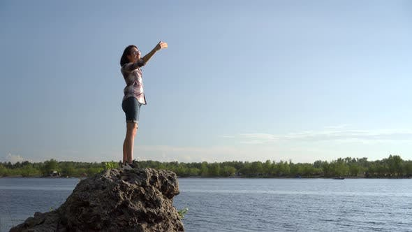 Thumbnail for A Young Woman Stands on a Stone and Takes Pictures of Herself on the Phone. The Girl Makes a Selfie