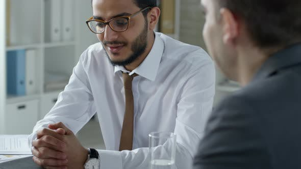 Cover Image for Cheerful Middle Eastern Businessman Talking with Male Colleague