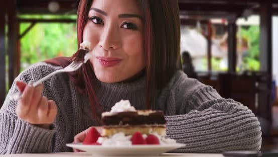 Thumbnail for Chinese woman eating cake at a restaurant