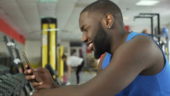 Thumbnail for Successful Smiling Athlete Scrolling Photos on Smartphone at Fitness Club