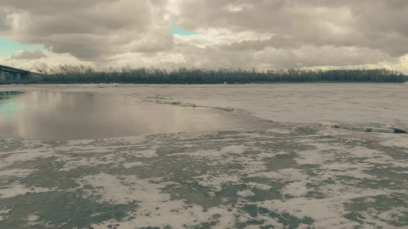 Pictorial Frozen River Against Bank with Dense Forest