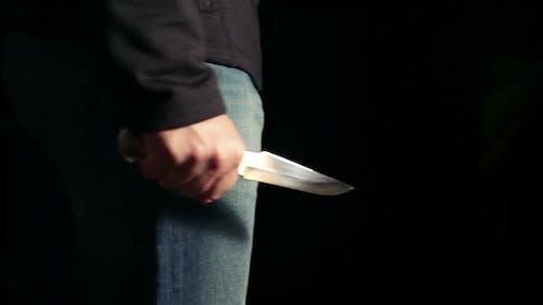 Ein Mann mit einem Messer in der Hand tritt in den Rahmen ein, bleibt stehen und geht dann weiter