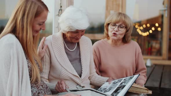 Thumbnail for Female Family Members Watching Pictures in Photo Album and Talking