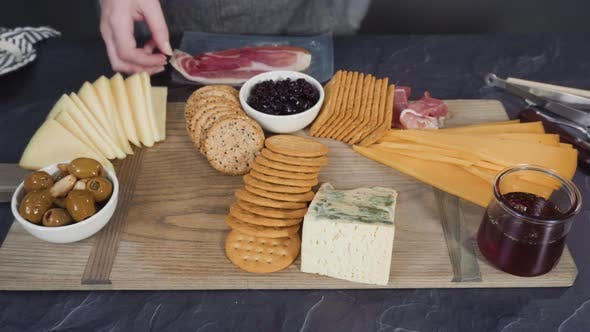 Arranging gourmet cheese, crakers, and fruits on a board for a large cheese board.