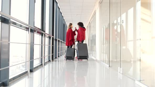 Couple with Suitcases Drinking Coffee at Airport