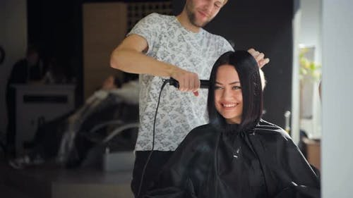Male Professional Hairdresser Is Straightening Brunette Woman's Hair Using a Hairstraightener in