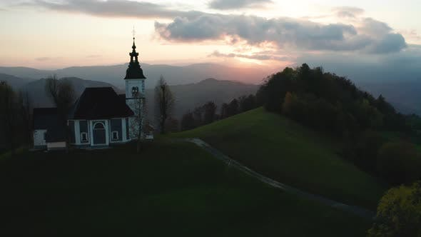 Cover Image for Amazing Beautiful Aerial View of the Hills, Colorful Forest and the Sv Sobota Church, Slovenia