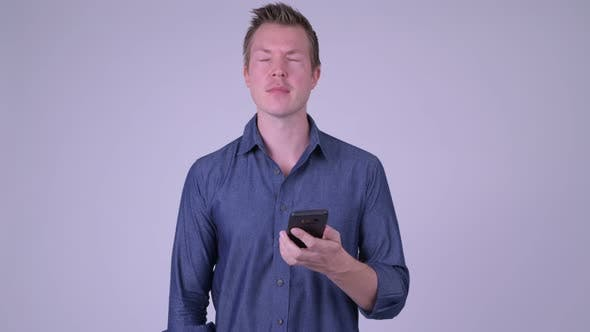 Cover Image for Stressed Young Businessman Using Phone and Getting Bad News