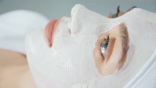 Woman Doing White Mask on Her Face in Wellness Spa Salon