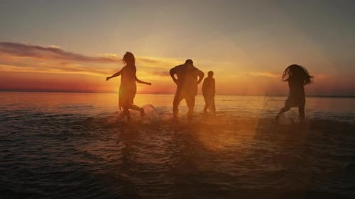Group of Happy People Stands and Playing in Water at the Beach on Sunset
