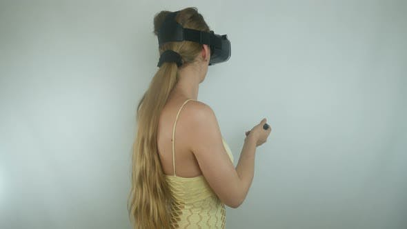 Thumbnail for Beautiful Woman Uses A Helmet Of Virtual Reality And A Gamepad In A Simulation Game