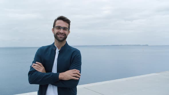 Thumbnail for Handsome Man In Glasses Folding Arms By Sea