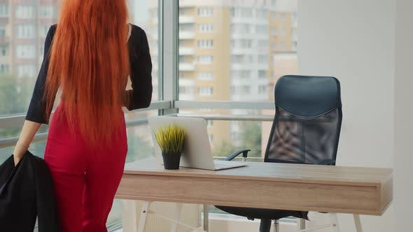 A Woman Who Came To Work and Starts Her Working Day in the Office By the Panoramic Windows Working