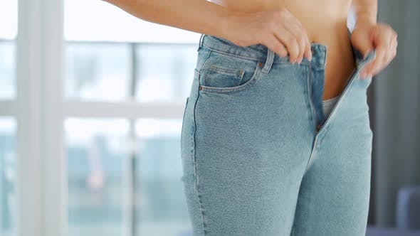 Woman Puts on Jeans in a Cozy Room