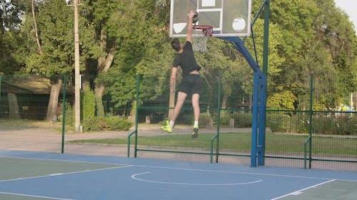 Junge Aktive männliche Basketballspieler in Sportbekleidung Fahren auf den Reifen mit Ball und Scoring Tor in