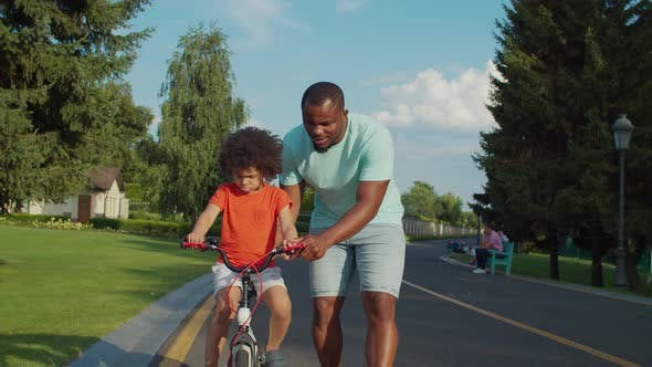 Thumbnail for Caring Dad Securing Little Boy at Balance Bike