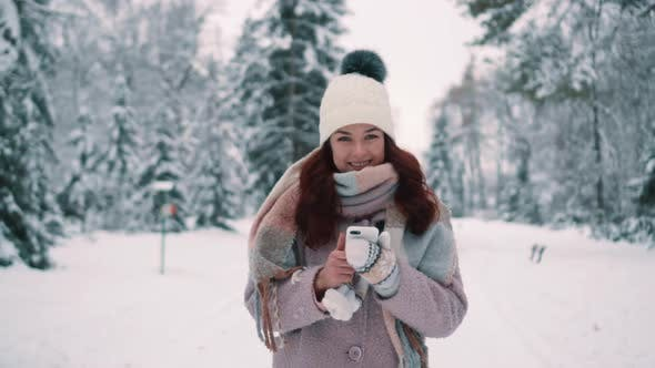 Thumbnail for Happy Woman Walking in Snow-covered Park Holding Smartphone