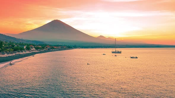 Sunset at Amed Beach with Boats and Yachts and Mountain Agung in Bali, Indonesia. Aerial Timelapse